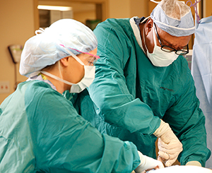 Healthcare providers performing surgery in operating room.