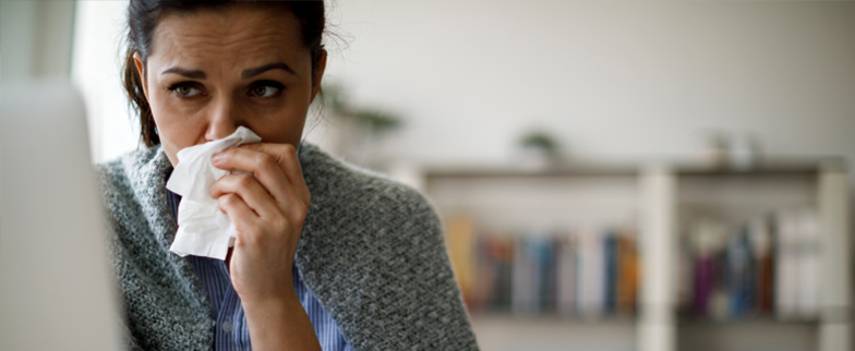 Woman sitting at her computer with a runny nose, tissue in hand