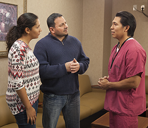 Healthcare provider talking to man and woman in hospital waiting room.