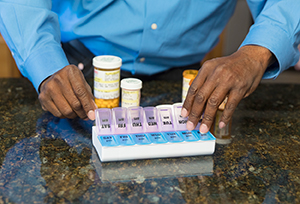 Man taking pill out of pill organizer.