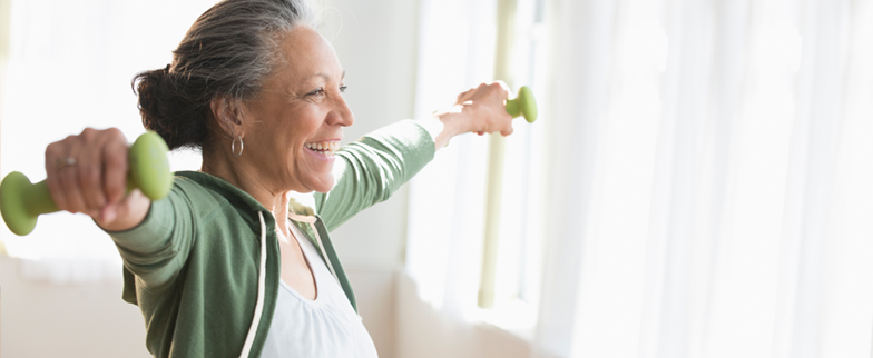 Older woman using hand weights at home
