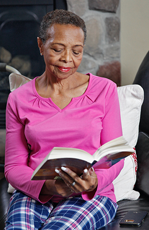 Woman sitting in chair, reading.