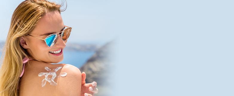 woman applying sunscreen to back